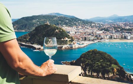 Drink glass white wine in male hands holidays looks top view city coast yacht from observation deck, romantic tourist man toast with alcohol panoramic cityscape downtown, person tourism san sebastian vacation enjoy travel