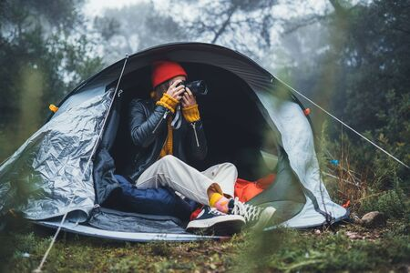 photographer tourist traveler take photo on camera in camp tent in foggy rain forest, hiker woman shooting mist nature trip, trekking tourism, rest vacation concept camping holiday Banque d'images - 132560104