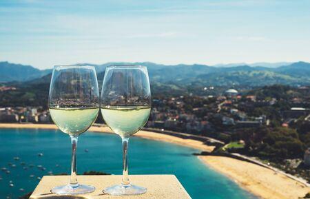 Dos vasos de vino blanco de copa de pie en el yate de la costa de la ciudad de vista superior del mar azul de fondo desde la plataforma de observación, brindis romántico con alcohol paisaje urbano panorámico en el centro de la ciudad, vacaciones de san sebastián de españa