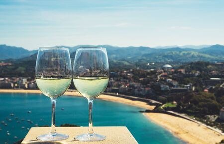 Two drink glass white wine standing on background blue sea top view city coast yacht from observation deck, romantic toast with alcohol panoramic cityscape downtown, spain san sebastian vacation