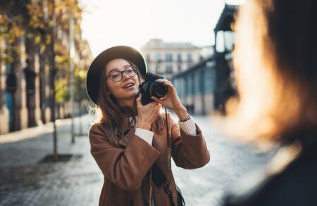 Fotograf w okularach z aparatem retro wziąć zdjęcie modelu dziewczyny. Turystyczna uśmiechnięta dziewczyna w kapeluszu podróżuje po Barcelonie na wakacjach z przyjacielem podróżnika. Ulica rozbłysku słonecznego w Europie. Koncepcja sesji zdjęciowej w mieście.
