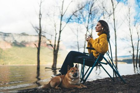 tourist traveler girl relax drink tea together dog on background foggy mountain, puppy pet hiker woman rest on lake shore nature trip, friendship love concept