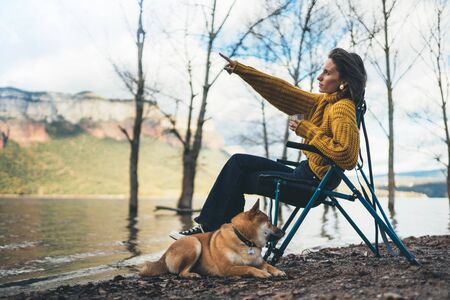 tourist traveler girl rest drink tea together dog on background mountain, puppy pet woman shows hand on lake shore nature trip, friendship concept