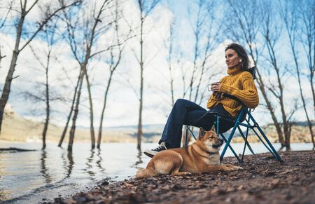 tourist traveler girl rest drink tea together dog on background mountain, puppy pet woman relax on lake shore nature trip, friendship concept