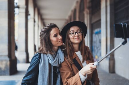 Smile girlfriends taking photo selfie on smartphone mobile. Blogger sisters travels in Barcelona. Holiday friendship concept. Travelers in glasses and hat self cellphone internet technology mockup