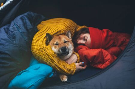 sleeping girl hug resting dog together in campsite, close up portrait red shiba inu leisure in camp tent , hiker woman with puppy dog relax nature vacation, friendship love concept