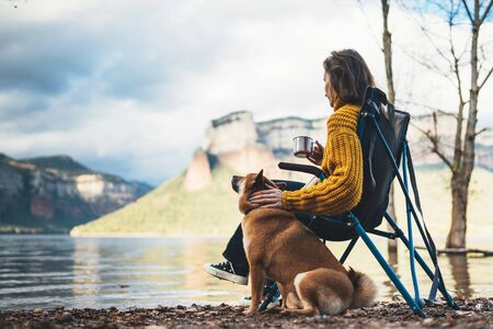 tourist traveler girl rest together dog on background mountain, woman drink tea hugging puppy pet on lake shore nature trip, friendship love concept