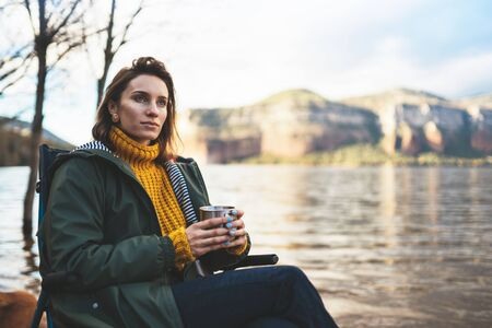 tourist traveler girl relax drink tea on background mountain, woman rest on lake shore nature trip, vacation concept