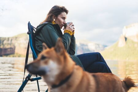 tourist traveler girl relax drink tea together dog on background mountain, puppy pet woman rest on lake shore nature trip, friendship concept