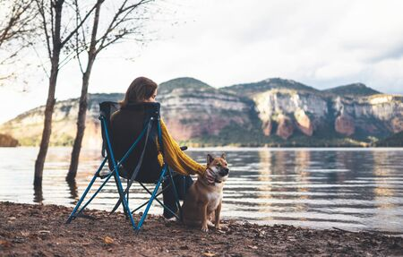 tourist traveler girl relax together dog on background mountain, puppy pet with woman rest on lake shore nature trip, friendship concept