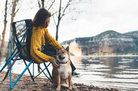 tourist traveler girl relax tender together friends dog on background mountain landscape,  woman hugging pet rest on lake shore nature trip