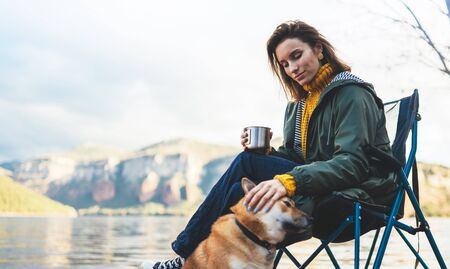 tourist traveler drink tea girl relax together dog on background mountain landscape,  woman hug pet rest on lake shore nature trip