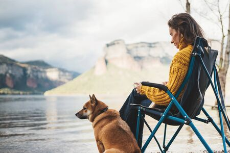 tourist traveler drink tea girl relax together dog mountain landscape,  woman hug pet rest on lake shore nature trip