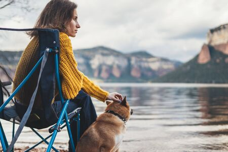 tourist traveler girl relax together dog on foggy mountain scape,  woman hug pet rest on lake shore nature trip