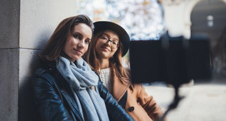 Girlfriends tourist taking photo selfie portrait together on smartphone mobile. Blogger hipster travels in europe city. Vacation holiday friendship concept. Travelers cellphone internet technology mockup space Stok Fotoğraf