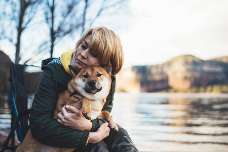 tourist traveler girl together dog on background mountain lake, happy woman hugging puppy pet nature, friendship love concept