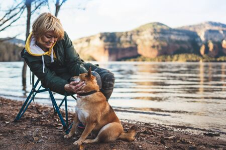 tourist traveler girl together dog on background mountain lake, happy smile woman hugging puppy pet nature, friendship love concept Stok Fotoğraf