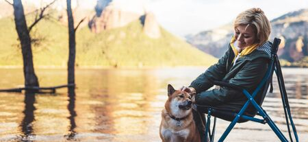 tourist traveler girl together dog on background mountain lake, happy smile woman hugging puppy pet nature, friendship love concept Stock fotó