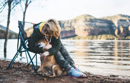 tourist traveler girl together dog on mountain lake, happy woman hugging puppy pet nature, friendship love concept