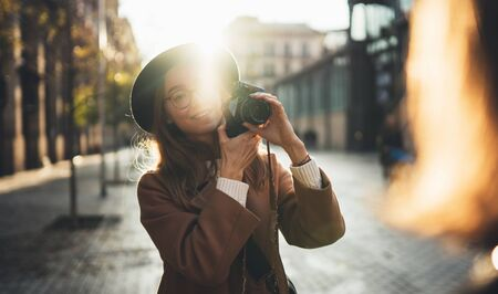 Photographer in glasses with retro camera take photo model girlfriend. Tourist smile girl in hat travels in Barcelona holiday with traveler friend. Sunlight street in europe. Photoshoot in sun city Stok Fotoğraf