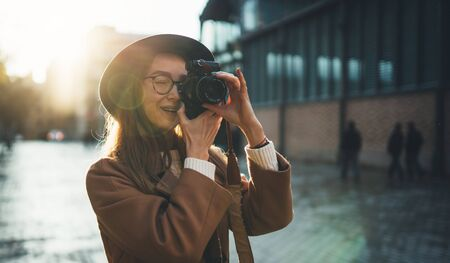 Outdoor smiling lifestyle portrait of pretty young woman having fun in sun city in Europe with camera travel photo photographer Making pictures in hipster style glasses and hat flare concept