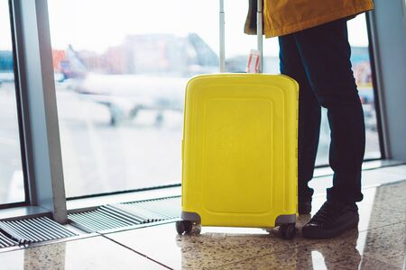 traveler with yellow suitcase backpack at airport on background window blue sky, passenger waiting flight in departure lounge area, hall of airport lobby terminal, vacation trip concept