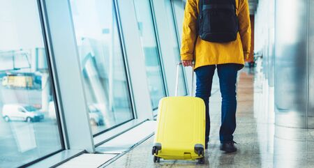 traveler with yellow suitcase backpack at airport on background window blue sky, passenger waiting flight in departure lounge area, airport lobby terminal, vacation trip concept Stok Fotoğraf