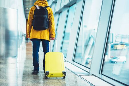 traveler with yellow suitcase backpack at airport on background large window blue sky, passenger waiting flight in departure lounge area, hall of airport terminal, vacation trip concept Stok Fotoğraf