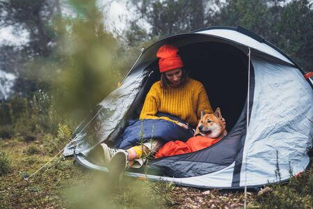 tourist traveler hugging relaxation red shiba inu in camp tent on background foggy forest, smile hiker woman with puppy dog in mist nature trip, friendship love concept, girl resting dog together Stock fotó