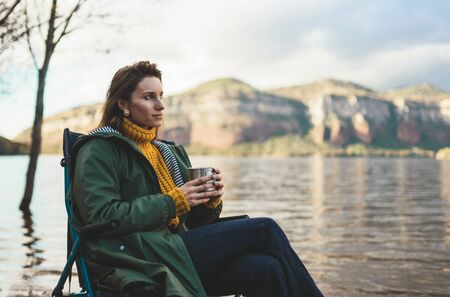 tourist traveler girl relax drink tea on background mountain,  woman think rest on lake shore nature trip, journey concept Stok Fotoğraf