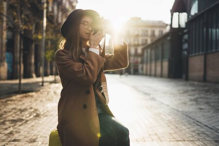 Tourist portrait. Girl in hat travels in Barcelona holiday. Photographer in glasses take photo on retro camera. Sunlight flare street in europe city. Traveler hipster shooting architecture, copy space mockup Stok Fotoğraf