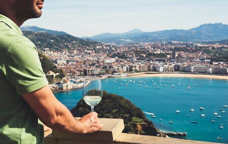 Drink glass white wine in male hands holidays looks top view city coast yacht from observation deck, tourist man toast with alcohol panoramic cityscape downtown, person tourism san sebastian vacation enjoy travel
