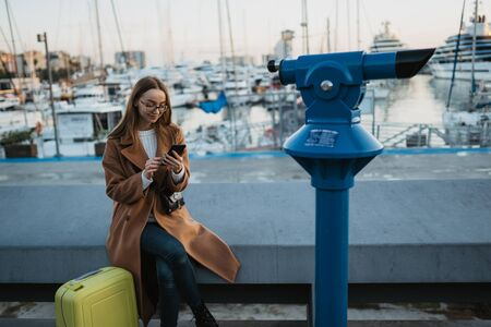 Traveler woman with suitcase calling mobile phone in evening sea port Barcelona with boat yacht. Girl tourist in glasses using smartphone technology online gadget cellphone in europe trip Stok Fotoğraf