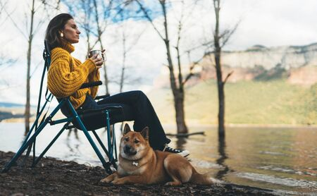 tourist traveler girl relax drink tea together dog on background mountain, puppy pet hiker woman rest on lake shore nature trip, friendship love concept Stok Fotoğraf