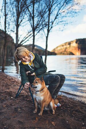 tourist traveler girl smile together dog on background mountain, fun woman hugging puppy pet on lake shore nature trip, friendship love concept Stok Fotoğraf