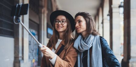 Smile girlfriends taking photo selfie on smartphone mobile. Blogger hipster travels in city. Holiday friendship concept. Travelers in glasses and hat self cellphone internet technology mockup space