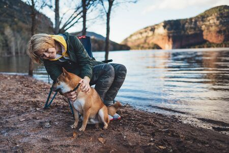 tourist traveler girl smile together dog on background mountain, happy woman hugging puppy pet on lake shore nature trip, friendship love concept Stok Fotoğraf