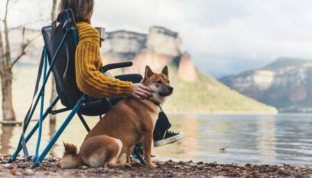 tourist traveler girl relax together friends dog on background mountain landscape,  woman hugging pet rest on lake shore nature trip