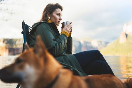tourist traveler girl relax drink tea together friends dog on background mountain scape, think woman with pet rest on lake shore nature trip Stok Fotoğraf