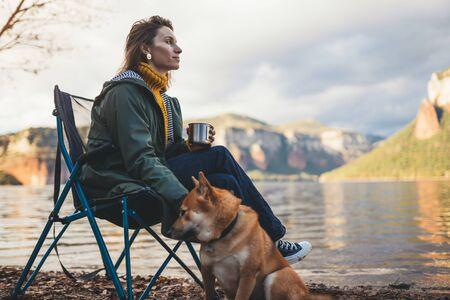 tourist traveler drink tea girl relax together dog on background mountain landscape,  woman hugging pet rest on lake shore nature trip Stok Fotoğraf