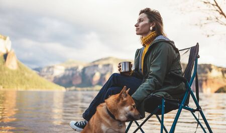 tourist traveler drink tea girl relax together dog on background mountain landscape,  woman hug pet rest on lake shore