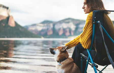 tourist think traveler relax together dog on mountain scape,  woman hug pet rest on lake shore nature trip Stok Fotoğraf