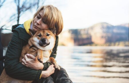 tourist traveler girl together dog on background mountain lake, happy woman hug puppy pet nature, friendship love concept Stock fotó