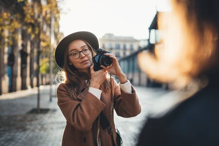 Hobby photographer concept. Outdoor lifestyle portrait of pretty young woman in sun city in Europe with camera travel photo of photographer in glasses and hat take photo model