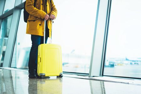traveler with suitcase backpack at airport on background window blue sky, passenger waiting flight in departure lounge area, hall of airport lobby terminal, vacation trip concept