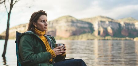 tourist traveler girl relax drink tea on background mountain landscape,  woman rest on lake shore nature trip, vacation concept Stok Fotoğraf