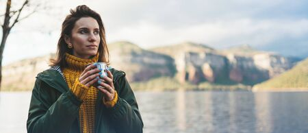 tourist traveler think girl relax drink tea on background mountain,  woman rest on lake shore nature trip, vacation concept