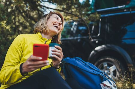 Young woman laughter showing teeth calling on mobile phone summer forest while traveling auto. Happy tourist smile with backpack holding on cellphone. Isolation girl using smartphone have fun emotion outdoors Foto de archivo