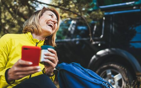 Woman laughter showing teeth calling on mobile phone summer forest while traveling auto. Happiness tourist with smile holding cellphone drink tea outdoors. Isolation girl using smartphone have fun emotions in park Foto de archivo