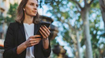 young businesswoman writes messages on smartphone while walking in a Barcelona Park on Sunny day, professional financier girl uses internet technology on mobile device outdoors